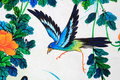 Het schilderen van de vogel op een muur Stock Fotografie