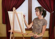 Het schilderen van de vrouw bij schildersezel Royalty-vrije Stock Foto