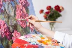 Het schilderen van een bos van bloemen stock afbeelding