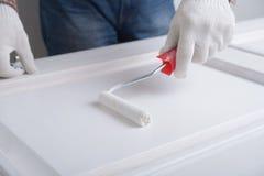 Het schilderen van een deur Stock Afbeeldingen