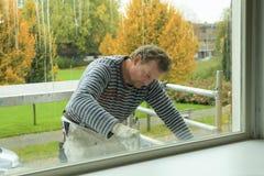 Het schilderen van een venster-kader Stock Foto's