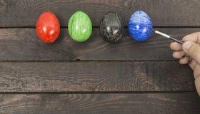 Het schilderen van hand kleurrijke eieren op houten achtergrond stock foto's