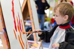 Het schilderen van het jonge geitje bij kleuterschool Stock Foto