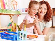 Het schilderen van het kind bij schildersezel. stock fotografie