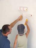 Het schilderen van het kind en van de vader muur samen Royalty-vrije Stock Afbeeldingen