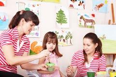 Het schilderen van het kind met leraar in kleuterschool. Stock Foto