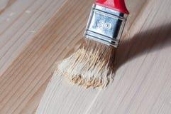 Het schilderen van hout met een borstel Stock Afbeelding