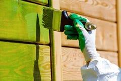 Het schilderen van houten muur gloved hand met verfborstel in groen royalty-vrije stock afbeelding