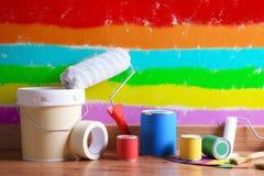 Het schilderen van hulpmiddelen op parketvloer met muur schilderde diverse kleuren stock foto
