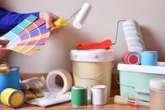 Het schilderen van hulpmiddelen voor huis en schilder die kleuren kiezen stock afbeelding