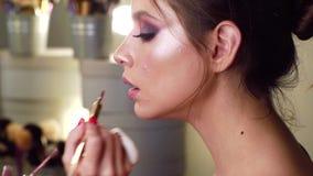 Het schilderen van lippen van jong schoonheids modelmeisje Professionele Grimeur die glamour modelmake-up doen op het werk Het co stock footage