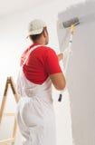 Het schilderen van muur met rol Stock Foto