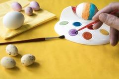 Het schilderen van paaseieren met rode borstel stock foto's