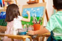 Het schilderen van sommige wolken in kunstklasse stock foto