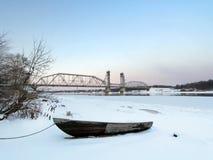 Het schip bemant boot op het strand bij de winterzonsondergang met de treinbrug op een achtergrond Stock Foto