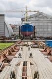 Het schip op de voorraden in scheepswerf stock foto's