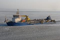 Het schip van de baggermachine in ijzige haven stock foto's