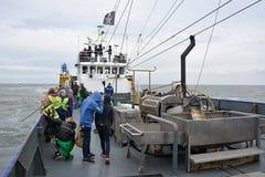Het schip van de garnalenvisserij op overzees met toeristenpassangers tijdens slecht weer stock afbeelding