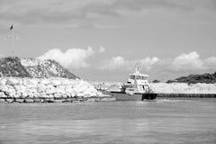 Het schip van de passagierscruise in overzees die baai met rotsachtige kust verlaten royalty-vrije stock foto's