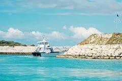 Het schip van de passagierscruise in overzees die baai met rotsachtige kust verlaten royalty-vrije stock afbeeldingen