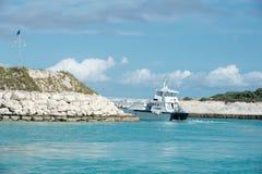 Het schip van de passagierscruise in overzees die baai met rotsachtige kust verlaten stock afbeeldingen