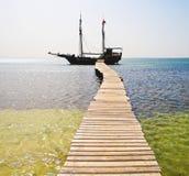 Het schip van de piraat onder heel Roger stock afbeeldingen
