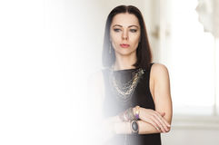 Het schitterende donkerharige in een zwarte kleding en massieve gouden juwelen bevindt zich in de witte ruimte Achtergrond Royalty-vrije Stock Afbeeldingen