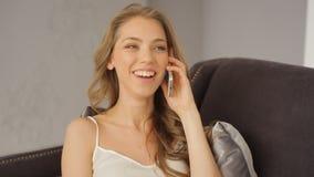 Het schitterende glamourmeisje spreekt op mobiele telefoon en lacht stock footage