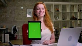 Het schitterende Kaukasische roodharige wijfje toont het groene scherm bij camera en glimlacht natuurlijk en gelukkig in helder stock footage