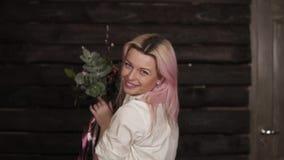Het schitterende roze haired meisje werpt in de emotioneel lucht omhoog een prachtig boeket van bloemen Het wervelen met bloemen  stock video