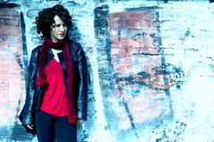 Het schitterende vrouw stellen met graffiti stock afbeeldingen