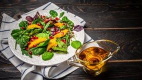 Het schone eten, detox, vegetarisch voedselconcept vegetarische salademango en granaatappel, vitaminesnack op een zwarte houten a royalty-vrije stock fotografie