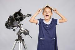 Het schoolmeisje behandelde haar hoofd met handboek en schreeuw bekijkend het kader, die zich bij de telescoop bevinden stock afbeelding