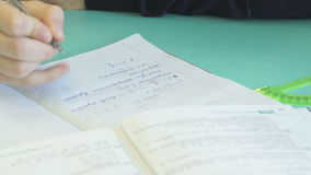 Het schoolmeisje beslist de huistaak in een notitieboekje stock footage