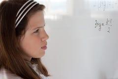 Het schoolmeisje denkt op vergelijkingsoplossing Stock Foto's