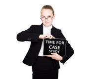 Het schoolmeisje in een pak houdt een PC-tablet in zijn handen met inschrijving - tijd voor gevallenanalyse stock fotografie