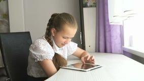 Het schoolmeisje gebruikt thuis een digitale tabletcomputer stock video
