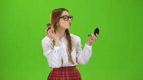 Het schoolmeisje in glazen poederde haar neus met een borstel Het groene scherm stock video