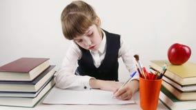 Het schoolmeisje glimlacht en schrijft bij lijst met boeken stock footage