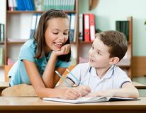 Het schoolmeisje helpt aan haar vriend om de taak te doen Stock Foto