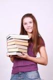 Het schoolmeisje houdt in hand boeken Stock Fotografie