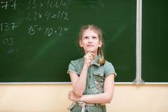 Het schoolmeisje in het klaslokaal die zich bij het bord bevinden lost een elementair voorbeeld in wiskunde op stock foto