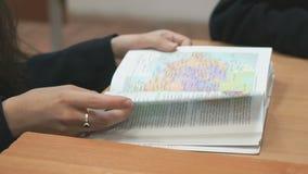 Het schoolmeisje knipt pagina's binnen weg van schoolhandboek stock videobeelden