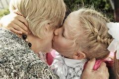 Het schoolmeisje kust teder grootmoeder op de dag terug naar school Stock Foto's