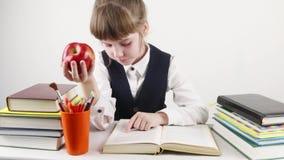 Het schoolmeisje leest boek en eet rode appel stock footage