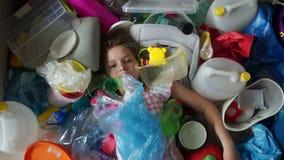 Het schoolmeisje ligt in een stapel van plastic afval, valt het afval op het meisje en behandelt haar gezicht, bereikt het kind u stock video