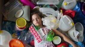 Het schoolmeisje ligt in een stapel van plastic afval, een plastic zakdalingen op het meisje Plastic verontreiniging van de plane stock footage