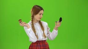 Het schoolmeisje maakt omhoog haar neus met een borstel gepoederd Het groene scherm stock videobeelden