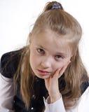 Het schoolmeisje met een nadenkende lucht stock foto's