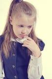 Het schoolmeisje met een nadenkende lucht royalty-vrije stock fotografie